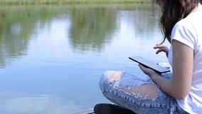 Girl Uses Digital Tablet. Near the river stock video