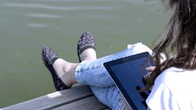 Girl Uses Digital Tablet. Woman uses digital tablet on a background of the river stock footage