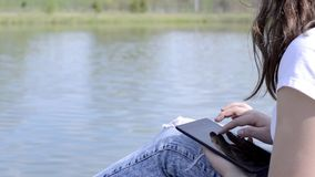 Girl Uses Digital Tablet. Woman uses digital tablet on a background of the river stock video