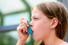 Girl uses an inhaler during an asthma attack. Close-up Stock Photo