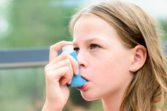 Girl uses an inhaler during an asthma attack Royalty Free Stock Photography