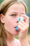 Girl uses an inhaler during an asthma attack Stock Image