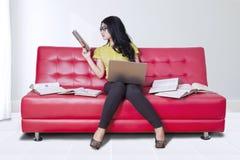 Girl uses laptop while reading books on sofa Stock Image