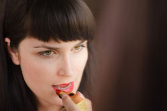 Girl uses lipstick red lipstick Royalty Free Stock Images