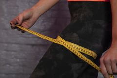 Girl uses a measuring cup to measure the body`s circumference stock images