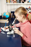 Girl uses a microscope and writes results Royalty Free Stock Image