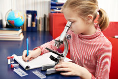 Girl uses a microscope and writes results Stock Photo
