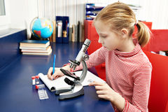 Girl uses a microscope and writes results Royalty Free Stock Images