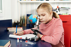 Girl uses a microscope and writes results Stock Photography