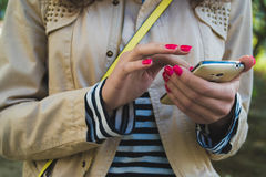 The girl uses the phone close up. She is dressed in a beige jacket and striped shirt, at the shoulder yellow strap from the bag. She holds a white phone with Royalty Free Stock Images