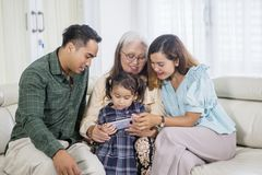Girl uses phone with parents and grandmother stock photos