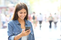 Girl uses a smart phone walking in the street. Happy girl uses a smart phone walking in the street of a big city Stock Photos