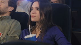 Girl uses smartphone at the movie theater stock footage