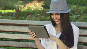 Girl uses tablet on the bench. Cute caucasian girl using tablet on the bench outdoors. Pretty brunette female teenager in gray hat flipping on touchscreen stock footage