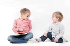 Girl uses tablet and boy playing with chalk Royalty Free Stock Photo