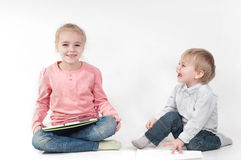 Girl uses tablet and boy playing with chalk Stock Photography