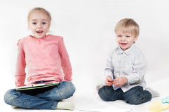 Girl uses a tablet and boy playing with chalk Royalty Free Stock Photo