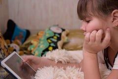Girl uses tablet computer. stock photo