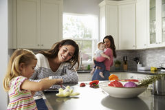 Girl uses tablet in kitchen with mum, other mum holding baby Royalty Free Stock Images