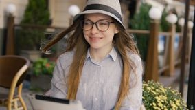 Girl Uses Tablet with Pleasure. Intelligent caucasian girl, in a grey striped hat, using silver tablet with pleasure in a cafe, outdoor slowmotion stock video footage