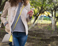 Girl uses a telephone in a beige jacket and blue jeans. The girl standing on the street in the spring on the background of trees, dressed in a beige jacket, blue Royalty Free Stock Photo