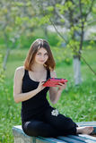 Girl uses touchpad on open air Royalty Free Stock Photography