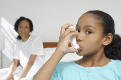 Girl Using Asthma Inhaler. Portrait of a girl using asthma inhaler with mother in background Stock Photos