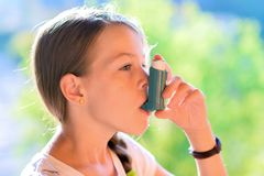 Girl using asthma inhaler. In a park Stock Image