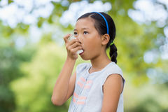 Girl using an asthma inhaler. In the park Royalty Free Stock Photography