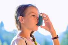 Girl using asthma inhaler in a park. Shallow depth of field stock photos