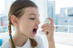 Girl using asthma pump. In clinic royalty free stock photo