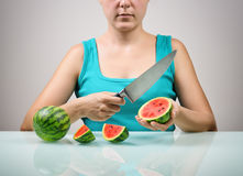 Girl using big knife for cutting ripe red small watermelons Stock Image