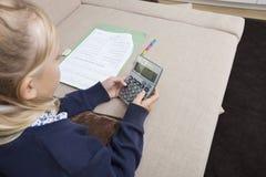 Girl using calculator while studying on sofa Stock Image