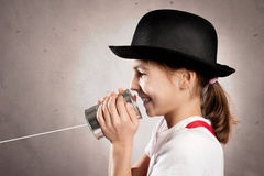 Girl using a can as telephone. Little girl using a can as telephone on a gray background Royalty Free Stock Image