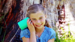Girl using a can phone. In a park stock video footage