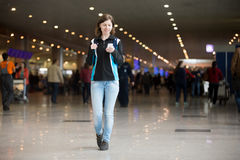 Girl using cell phone in airport Stock Image