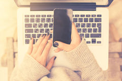 Girl using cell phone and laptop stock image