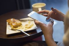 Girl using cellphone at breakfast Stock Image