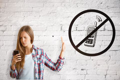 Girl using cellphone. European girl on white brick background using cellphone despite the inhibitory sign. Addiction concept stock photo