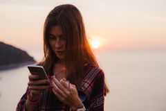 Girl using cellphone near the sea in sunrise or sunset. Royalty Free Stock Images