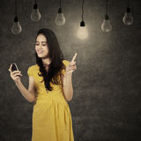 Girl using cellphone under lamps. Portrait of pretty girl reading message on the cellphone under lamps Royalty Free Stock Photo