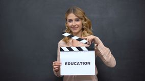 Girl using clapperboard with word Education, start of school year, graduation. Stock footage stock footage