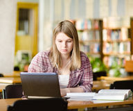 Girl using computer in a library Royalty Free Stock Photos