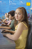 Girl Using Computer Mouse. Portrait of a cute girl using computer mouse with classmates in the background Stock Image