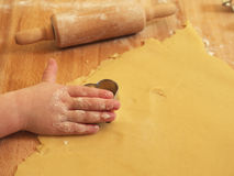 Girl using cookie cutter. Photo shows a close up of a small kids hand using the cookie cutter Stock Images