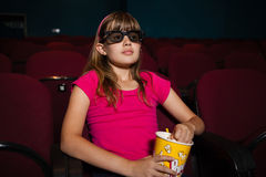 Girl using 3D glasses while having popcorns during movie Royalty Free Stock Image