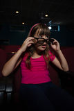 Girl using 3D glasses while watching movie Royalty Free Stock Image