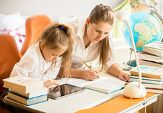 Girl using digital tablet while mother doing homework instead of Royalty Free Stock Photos