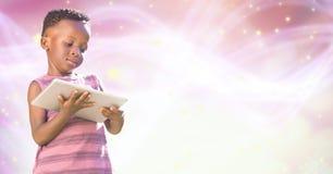 Girl using digital tablet over pink glowing bokeh Royalty Free Stock Photos