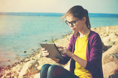 Girl using digital tablet at sea Royalty Free Stock Photography